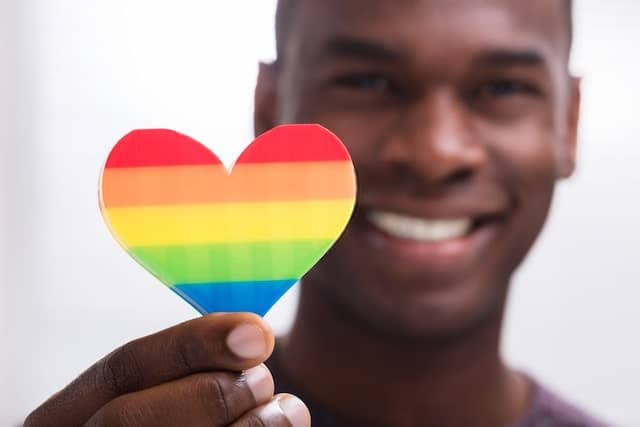 African Man Holding a Rainbow Heart