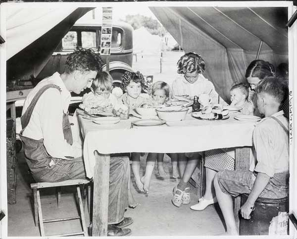 Okie Family Driven from their Land by the Dustbowl Preparing to Eat in a Transient Camp in California