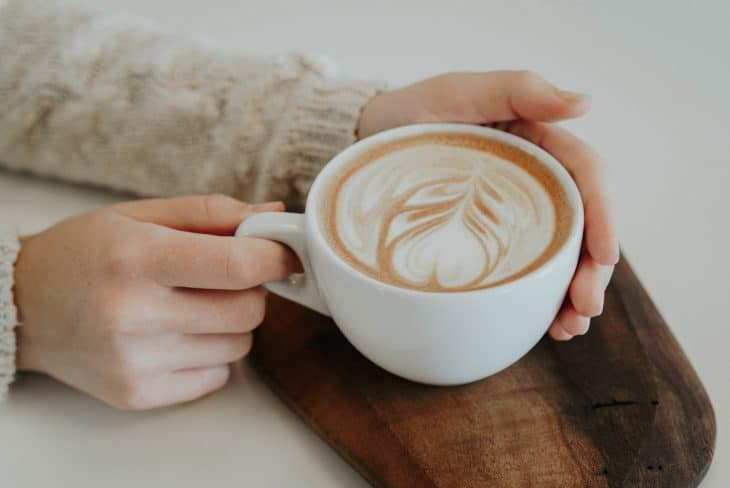 woman holding coffee, coffee facts