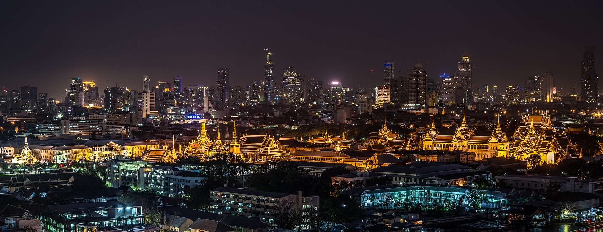 The Grand Palace amidst the Bangkok skyline at night.